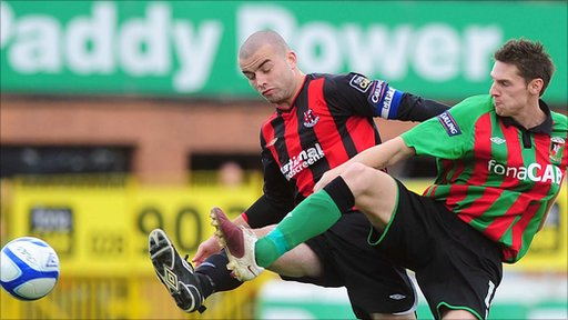 Crusaders' Colin Coates and Glentoran's Dary Fordyce wrestle for control of the ball