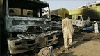 Pakistanis search for items beside burnt-out oil tankers