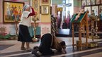 A woman crosses herself while another kisses the floor in the Church of St Michael the Archangel