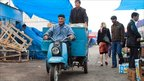 A man rides his moped through the market