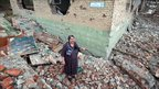 A woman stands amongst rubble in Grozny