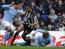 Manchester City's Nigel de Jong (right) tackles Newcastle's Hatem Ben Arfa