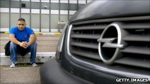 A worker sits outside the Opel factory in Antwerp