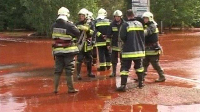 Firemen standing in the sludge