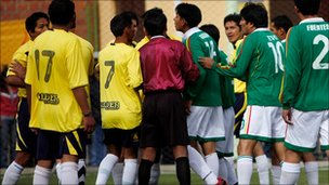 President Morales in a group of players arguing with the referee