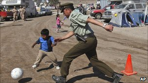 A police officer and child play football at the camp where relatives of trapped miners wait for news in Copiapo, Chile on Sunday