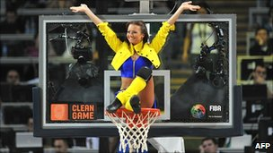 A cheerleader balances on a basketball hoop