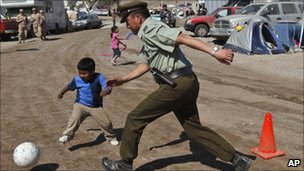 A police officer and a child play football at the camp where relatives of trapped miners wait for news outside the San Jose in Copiapo, Chile