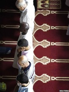 Muslim men attend a mass prayer session during Ramadan in Algiers in August 2010