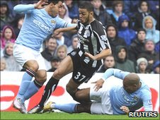 Nigel de Jong (left) slides in to tackle Hatem Ben Arfa as Carlos Tevez (left) looks on