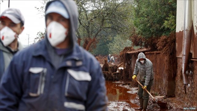 Residents clear up toxic sludge in the flooded village of Devecser