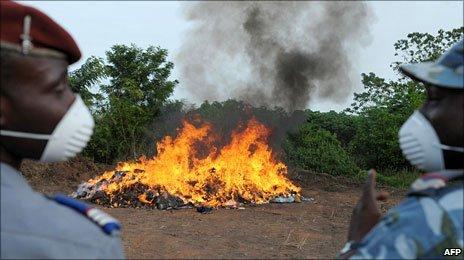 Ivory Coast drug enforcement gendarmes watch as bags of seized cannabis burns (June, 2009)