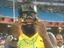 Jamaican Ramone McKenzie shows off his Batman mask during the 100m heats