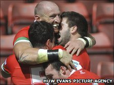 Try-scorer Gareth Thomas is congratulated by his new Wales team-mates
