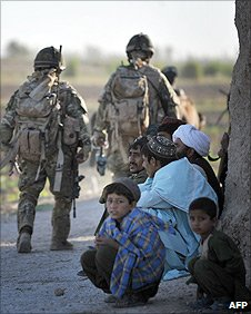 Afghan residents look on as soldiers patrol their village in Helmand province