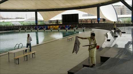 An Indian worker cleans the pool