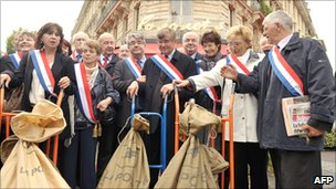 French mayors and members of the French Communist Party stand near trolleys carrying post bags full of petitions against the pension reforms that they are bringing to the Elysee Palace on 6 October 2010 in Paris