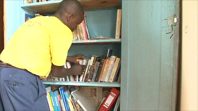 Boy looks through books on shelf