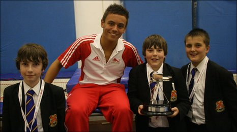 Tom Daley shows off his Young Sports Personality trophy to students