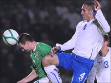 David Healy is challenged by Italy defender Giorgio Chiellini