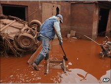 Man in western Hungary inspects damage caused by toxic red sludge
