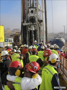 Rescue workers celebrate next to the Plan B drill after it reaches the workshop (9 October 2010)