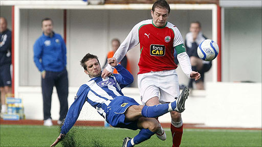 Newry City defender Cullen Feeney tackles Cliftonville striker Chris Scannell