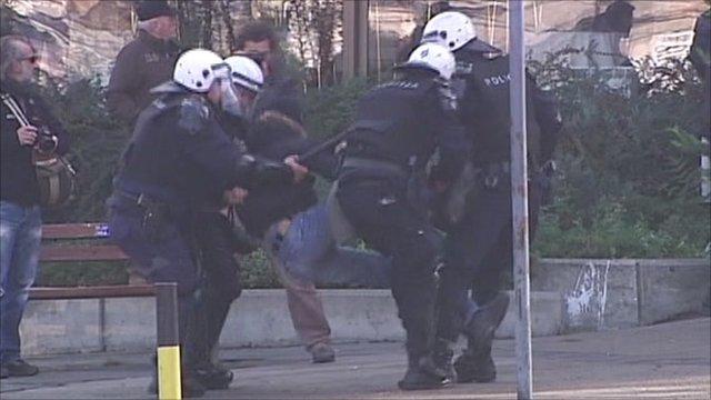 Police in Belgrade tackle a protestor