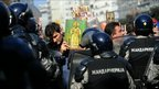 An anti-gay protesters in Belgrade holds an Orthodox religious symbol in front of police