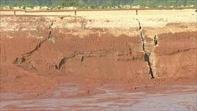 Cracks widened at a burst reservoir that spilled toxic sludge