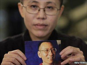 Liu Xia, the wife of Chinese dissident Liu Xiaobo, holds a photo of Liu Xiaobo