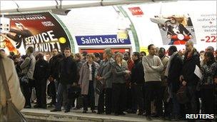 Commuters wait at Paris St Lazare station