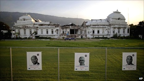 Photos of Lesley Voltaire, left, Charles Henry Baker, centre, and  Jean Hector Anacasis, all running for the presidency, are stuck on a  fence surrounding the earthquake-damaged National Palace in  Port-au-Prince, Haiti