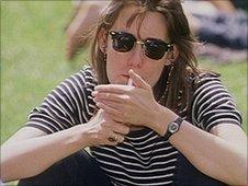 Woman lights cigarette