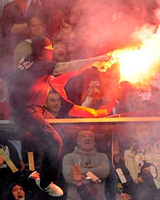 A mask-wearing Serbian fan sets off a flare in the stadium