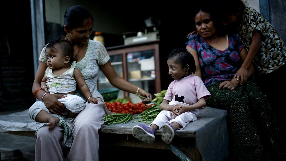 Khagendra Thapa Magar sits outside his parents' vegetable shop with his mother and a young woman and her one-year-old child (Photo by Tom van Cakenberghe)