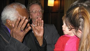 Archbishop Tutu playing peek-a-boo with David Epstein's son
