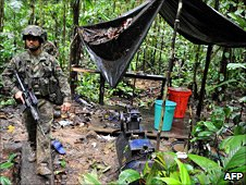 A Colombian army soldier walks next to a cocaine laboratory in the jungle