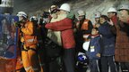 Chilean miner Florencio Avalos is embraced by President Sebastian Pinera as his family wait nearby