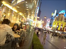 A couple eat in the window of a restaurant in a pedestrianised shopping mall in Shanghai