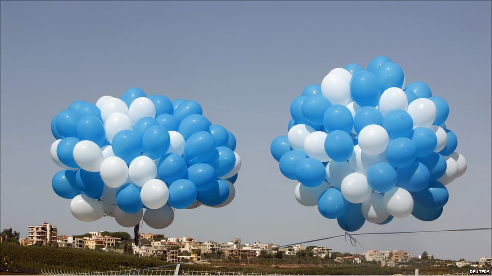 The Lebanese town of Kfar Kila is seen in the background before Israelis release balloons near the border in the town of Metulla in protest against Mr Ahmadinejad's visit to Lebanon, 13 October 2010