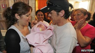 Chilean miner Ariel Ticona (wearing cap), his wife Elizabeth Segovia and their baby girl Esperanza, who was born while Ticona was trapped in the San Jose mine - 15 October 2010