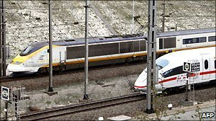 A German ICE high-speed train (white) crosses an Eurostar train before entering the Channel tunnel