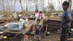Soriano family by the remains of their home in Delfin Albano township, Isabela province, Philippines (19 Oct 2010)