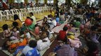 Families displaced by Typhoon Megi take temporary shelter in a sports complex on 19 October 2010