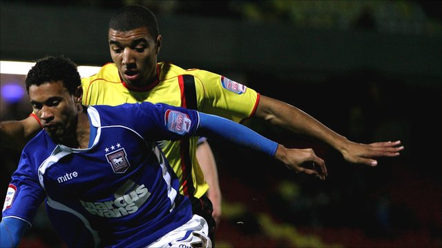 Troy Deeney of Watford chases Carlos Edwards of Ipswich