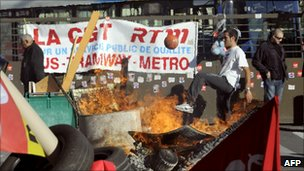 A bus driver in Marseille kicking a ball behind a fire at the entrance to the Capelette bus depot, blocked by CGT union members