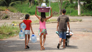 Children collect fresh water at their temporary housing camp