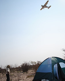 A plane flies above Jonah Fisher's tent