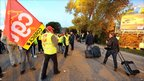 People walk with their luggage next to strikers as they block access to Marseille's Marignane airport